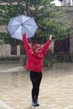 有伞跳舞的年轻愉快的妇女在雨中 免版税库存图片
