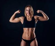 有伟大的肌肉的运动的女孩在黑运动服 被晒黑的年轻运动妇女 巨大体育女性身体 库存图片