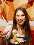 有传神张的嘴的美丽的妇女吃意大利细面条的 库存照片