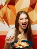 有传神张的嘴的美丽的妇女吃意大利细面条的 免版税图库摄影
