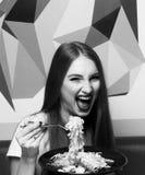 有传神张的嘴的美丽的妇女吃意大利细面条的 图库摄影