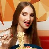 有传神张的嘴的美丽的妇女吃意大利细面条的 免版税库存图片