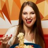 有传神张的嘴的美丽的妇女吃意大利细面条的 免版税库存照片