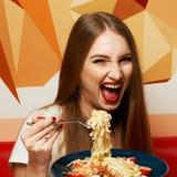 有传神张的嘴的美丽的妇女吃意大利细面条的 库存图片