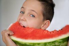 有传神眼睛的白种人男孩,采取一个水多的西瓜的叮咬 免版税库存图片