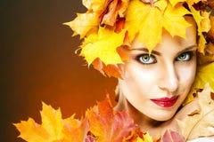 有传神面部特点的美丽的妇女在黄色槭树离开 免版税库存照片