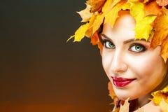 有传神面部特点的美丽的妇女在黄色槭树离开 免版税图库摄影