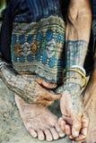 有传统纹身花刺的年长部族妇女在她的家前面 库存照片