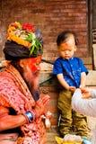 有传统被绘的面孔和colouful衣裳的圣洁Sadhu人保佑孩子在Pashupatinath印度寺庙复杂近的K 免版税库存照片
