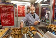 有传统髭的更老的香肠供营商在巴伐利亚转动剁碎的小牛肉和猪肉食物 免版税图库摄影
