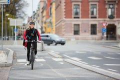 有传讯者交付袋子的女性骑自行车者在街道上 库存照片