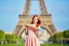 有传统法国面包长方形宝石的女孩在埃佛尔铁塔前面 库存照片