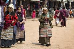 有传统绳索的尼泊尔妇女在朝圣走围绕著名吸引力佛教寺庙Boudhanath Stupa的小组, 免版税库存图片