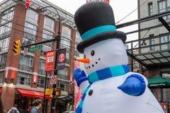 有伤痕、高帽子和红萝卜鼻子的巨型爆炸雪人在街市温哥华,Yaletown的 库存照片