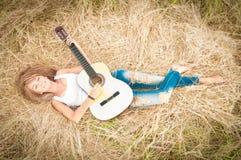 有位于在草的吉他的愉快的女孩在草甸。 免版税库存照片