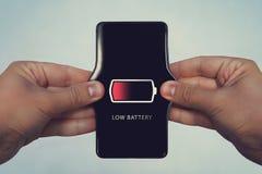 有低电池的手机在屏幕上 所有屏幕图表组成 增加电池功率,微弱的充电 人的手stretc 库存图片