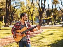 有低音吉他的人在公园 图库摄影