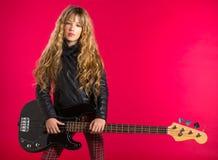 有低音吉他的白肤金发的摇滚乐女孩在红色 免版税库存图片