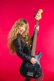 有低音吉他的白肤金发的摇滚乐女孩在红色 免版税库存照片