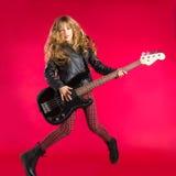 有低音吉他跃迁的白肤金发的摇滚乐女孩在红色 库存图片