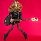 有低音吉他跃迁的白肤金发的摇滚乐女孩在红色 库存照片
