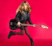 有低音吉他跃迁的白肤金发的摇滚乐女孩在红色 免版税库存照片