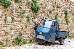 有住宅的美丽如画的老胡同和一辆古老意大利车模仿比雅久 免版税库存照片