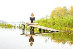 有体育性感的形象的女孩在镇静秋天河背景  瑜伽,凝思,放松 库存图片