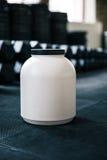 有体育营养的塑胶容器在哑铃 免版税图库摄影