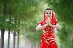 有佛教姿态的亚裔中国秀丽肚皮舞表演者  库存照片