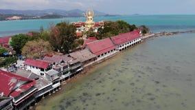 有佛教寺庙和许多房子的海岛 海岛鸟瞰图有佛教寺庙的有雕象的大菩萨 股票视频