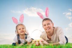 有作为复活节兔子打扮的母亲的小女孩说谎在 库存照片