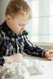 有作家块的男孩奋斗与家庭作业的 库存照片