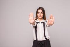 有作报告的坏态度的特写镜头画象年轻懊恼恼怒的妇女与棕榈向外被隔绝的灰色墙壁后面的手势 库存图片