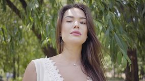 有佩带一个长的白色夏天时尚礼服身分的长的深色的头发的画象可爱的少女在下 影视素材