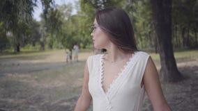 有佩带一个长的白色夏天时尚礼服身分的长的深色的头发的画象可爱的少女在分支下 影视素材