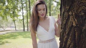 有佩带一个长的白色夏天时尚礼服身分的长的深色的头发的画象可爱的少女在树旁边 股票录像