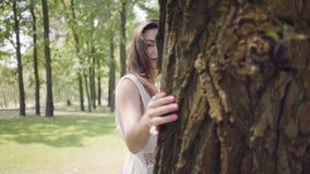 有佩带一个长的白色夏天时尚礼服身分的长的深色的头发的画象迷人的少女在树旁边 股票录像