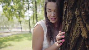 有佩带一个长的白色夏天时尚礼服身分的长的深色的头发的画象迷人的少女在树旁边 影视素材