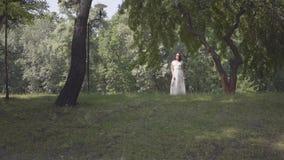 有佩带一个长的白色夏天时尚礼服身分的长的深色的头发的逗人喜爱的少女在树的分支下 股票录像