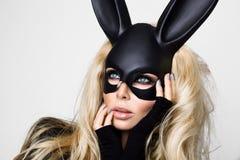 有佩带一只黑面具复活节兔子的大乳房的性感的妇女站立在白色背景 免版税库存照片