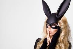 有佩带一只黑面具复活节兔子的大乳房的性感的妇女站立在白色背景 免版税图库摄影