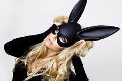 有佩带一只黑面具复活节兔子的大乳房的性感的妇女站立在白色背景 免版税库存图片