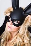 有佩带一只黑面具复活节兔子的大乳房的性感的妇女站立在白色背景 库存照片