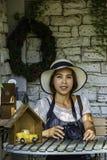 有佩带一台帽子和照相机在桌背景白色砖墙上的短发的亚裔妇女 库存图片