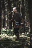 有佩带传统战士的剑和锤子的北欧海盗妇女在一个深神奇森林穿衣 库存照片