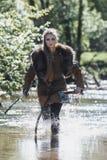 有佩带传统战士的剑和锤子的北欧海盗妇女在一个深神奇森林穿衣 免版税库存图片