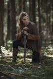 有佩带传统战士的剑的北欧海盗妇女在一个深神奇森林穿衣 库存照片