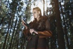 有佩带传统战士的锤子的北欧海盗妇女在一个深神奇森林穿衣 免版税库存照片