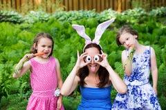 有佩带兔宝宝耳朵和傻的眼睛的孩子的滑稽的母亲 库存图片